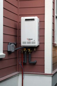 "Figure 4. A whole-house tankless natural gas water heater installed outdoors showing its more simple venting system. Credit: Flickr user ""omiksemaj"" (CC BY-NC 2.0)."