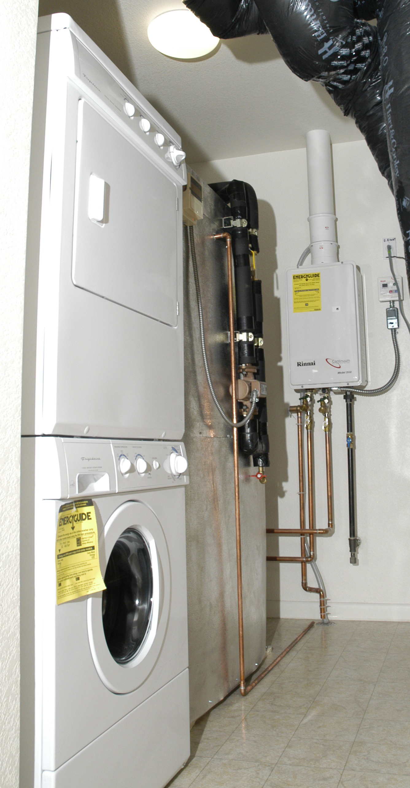 a wholehouse tankless gas water heater installed in a laundry room
