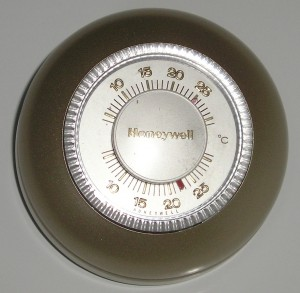 """Figure 1. A familiar example – the round mechanical thermostat. Credit:<a title=""""Honeywell thermostat"""" href=""""https://commons.wikimedia.org/wiki/File:Honeywell_thermostat.jpg"""" target=""""_blank"""">Vincent de Groot / Wikimedia Commons, CC BY 2.5</a>."""