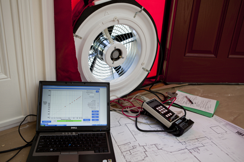 Figure 2. A view from the inside of the home showing the blower door test equipment: a temporary door (frame), blower (fan), and manometer (pressure gauge) along with helpful tools including a laptop computer, clipboard and blueprints of the home. Credit: PREC
